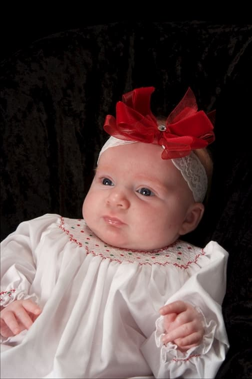 baby-girl-in-Christmas-outift-with-red-bow